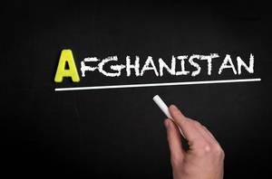 """Hand schreibt das Wort """"Afghanistan"""" mit Kreide auf eine schwarze Tafel"""