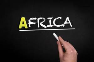 """Hand schreibt das Wort """"Afrika"""" mit Kreide auf eine schwarze Tafel"""