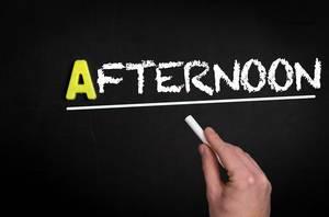 """Hand schreibt das Wort """"Afternoon"""" - Nachmittag - mit Kreide auf eine schwarze Tafel"""