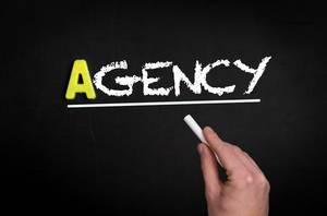 """Hand schreibt das Wort """"Agency"""" - Agentur - mit Kreide auf eine schwarze Tafel"""