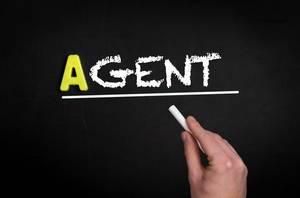 """Hand schreibt das Wort """"Agent"""" mit Kreide auf eine schwarze Tafel"""