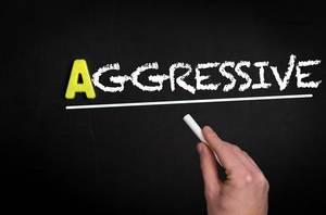 """Hand schreibt das Wort """"Aggressiv"""" mit Kreide auf eine schwarze Tafel"""