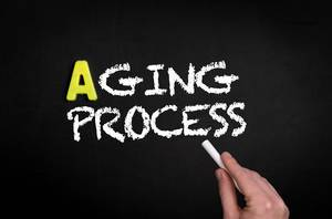 """Hand schreibt das Wort """"Aging Process"""" - Alterungsprozess - mit Kreide auf eine schwarze Tafel"""