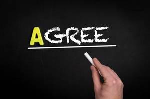 """Hand schreibt das Wort """"Agree"""" - Zustimmen - mit Kreide auf eine schwarze Tafel"""