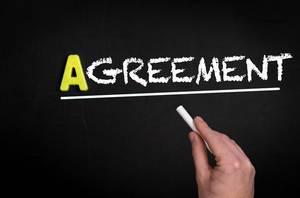 """Hand schreibt das Wort """"Agreement"""" - Zustimmung - mit Kreide auf eine schwarze Tafel"""