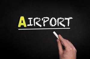 """Hand schreibt das Wort """"Airport"""" - Flughafen - mit Kreide auf eine schwarze Tafel"""