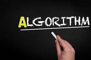 """Hand schreibt das Wort """"Algorithmus"""" mit Kreide auf eine schwarze Tafel"""