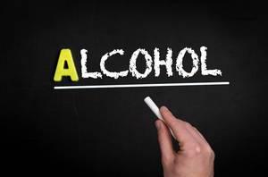 """Hand schreibt das Wort """"Alkohol"""" mit Kreide auf eine schwarze Tafel"""