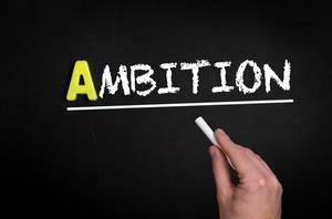 """Hand schreibt das Wort """"Ambition"""" mit Kreide auf eine schwarze Tafel"""