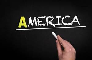 """Hand schreibt das Wort """"Amerika"""" mit Kreide auf eine schwarze Tafel"""