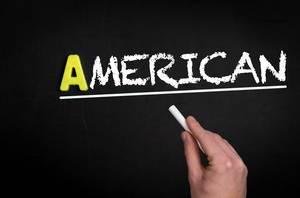 """Hand schreibt das Wort """"Amerikanier"""" mit Kreide auf eine schwarze Tafel"""