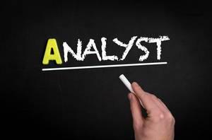 """Hand schreibt das Wort """"Analyst"""" mit Kreide auf eine schwarze Tafel"""