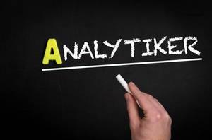 """Hand schreibt das Wort """"Analytiker"""" mit Kreide auf eine schwarze Tafel"""