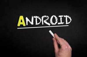 """Hand schreibt das Wort """"Android"""" mit Kreide auf eine schwarze Tafel"""