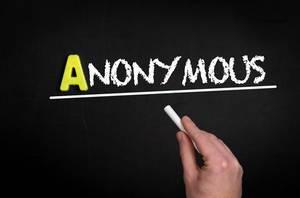 """Hand schreibt das Wort """"Anonymous"""" - anonym - mit Kreide auf eine schwarze Tafel"""
