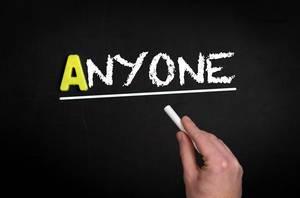 """Hand schreibt das Wort """"Anyone"""" - Irgendjemand - mit Kreide auf eine schwarze Tafel"""