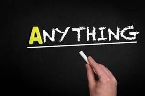 """Hand schreibt das Wort """"Anything"""" - Irgendetwas - mit Kreide auf eine schwarze Tafel"""