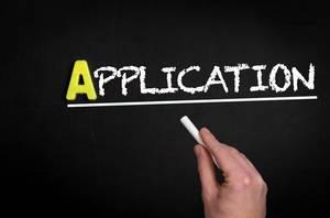 """Hand schreibt das Wort """"Application"""" - Bewerbung / Antrag / Anwendung - mit Kreide auf eine schwarze Tafel"""