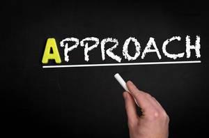 """Hand schreibt das Wort """"Approach"""" - Konzept / Ansatz - mit Kreide auf eine schwarze Tafel"""