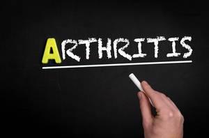 """Hand schreibt das Wort """"Arthritis"""" mit Kreide auf eine schwarze Tafel"""