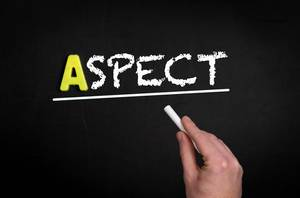 """Hand schreibt das Wort """"Aspekt"""" mit Kreide auf eine schwarze Tafel"""