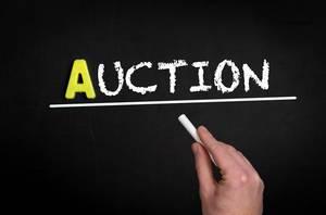 """Hand schreibt das Wort """"Auction"""" - Auktion / Versteigerung - mit Kreide auf eine schwarze Tafel"""