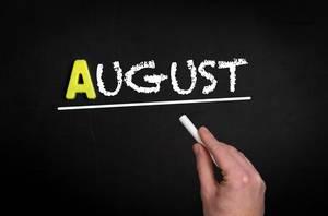 """Hand schreibt das Wort """"August"""" mit Kreide auf eine schwarze Tafel"""
