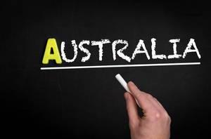 """Hand schreibt das Wort """"Australien"""" mit Kreide auf eine schwarze Tafel"""