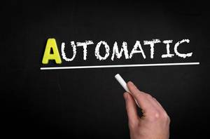 """Hand schreibt das Wort """"Automatic"""" - automatisch - mit Kreide auf eine schwarze Tafel"""