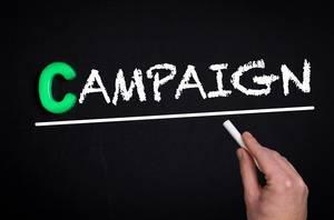 """Hand schreibt das Wort """"Campaign"""" - Kampagne - mit Kreide auf eine schwarze Tafel"""