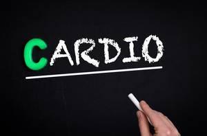 """Hand schreibt das Wort """"Cardio"""" mit Kreide auf eine schwarze Tafel"""