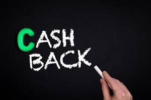 """Hand schreibt das Wort """"Cashback"""" mit Kreide auf eine schwarze Tafel"""