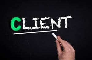 """Hand schreibt das Wort """"Client"""" - Klient / Kunde - mit Kreide auf eine schwarze Tafel"""