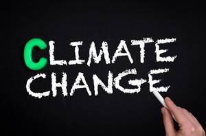 """Hand schreibt das Wort """"Climate Change"""" - Klimawandel - mit Kreide auf eine schwarze Tafel"""