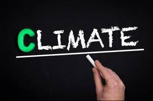 """Hand schreibt das Wort """"Climate"""" - Klima - mit Kreide auf eine schwarze Tafel"""