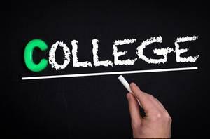 """Hand schreibt das Wort """"College"""" mit Kreide auf eine schwarze Tafel"""
