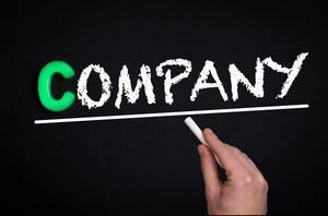 """Hand schreibt das Wort """"Company"""" - Firma - mit Kreide auf eine schwarze Tafel"""