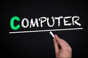 """Hand schreibt das Wort """"Computer"""" mit Kreide auf eine schwarze Tafel"""