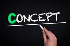 """Hand schreibt das Wort """"Concept"""" - Konzept - mit Kreide auf eine schwarze Tafel"""