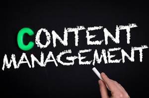 """Hand schreibt das Wort """"Content-Manager"""" mit Kreide auf eine schwarze Tafel"""