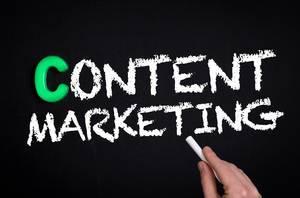 """Hand schreibt das Wort """"Content-Marketing""""  mit Kreide auf eine schwarze Tafel"""
