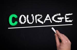 """Hand schreibt das Wort """"Courage"""" mit Kreide auf eine schwarze Tafel"""