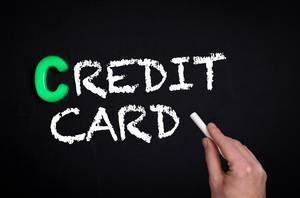 """Hand schreibt das Wort """"Credit Card"""" - Kreditkarte - mit Kreide auf eine schwarze Tafel"""