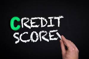 """Hand schreibt das Wort """"Credit Score"""" - Bonität / Kreditwürdigkeit - mit Kreide auf eine schwarze Tafel"""