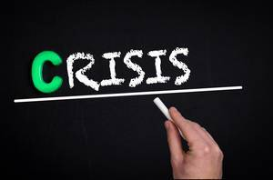 """Hand schreibt das Wort """"Crisis"""" - Krise - mit Kreide auf eine schwarze Tafel"""