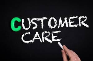 """Hand schreibt das Wort """"Customer Care"""" - Kundenbetreuung - mit Kreide auf eine schwarze Tafel"""