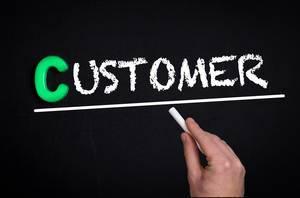 """Hand schreibt das Wort """"Customer"""" - Kunde - mit Kreide auf eine schwarze Tafel"""