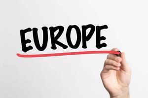 """Hand schreibt das Wort """"Europa"""" auf ein Whiteboard"""