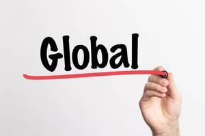 """Hand schreibt das Wort """"Global / Weltweit"""" auf ein Whiteboard"""