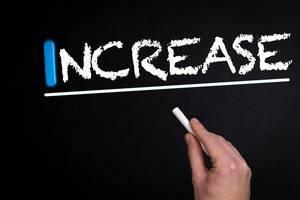 """Hand schreibt das Wort """"Increase"""" - Erhöhen - mit Kreide auf eine schwarze Tafel"""